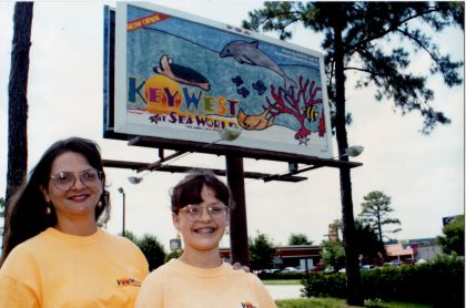 Kim Peters and Ashley Peters in front of Ashley's billboard.